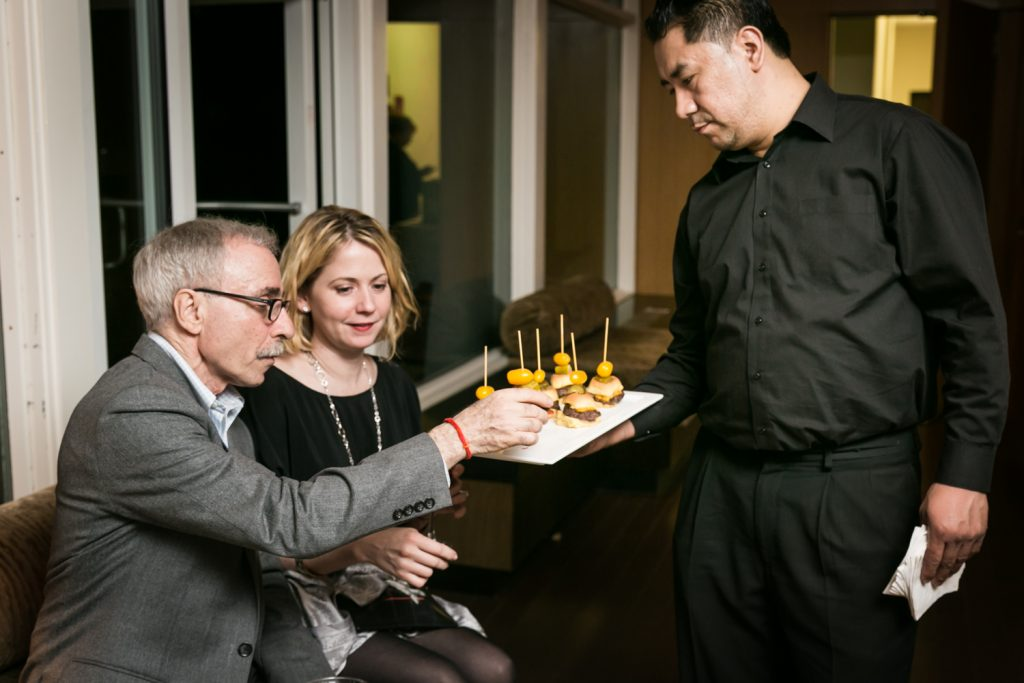 Birthday party photos of couple selecting mini hamburger from appetizer tray