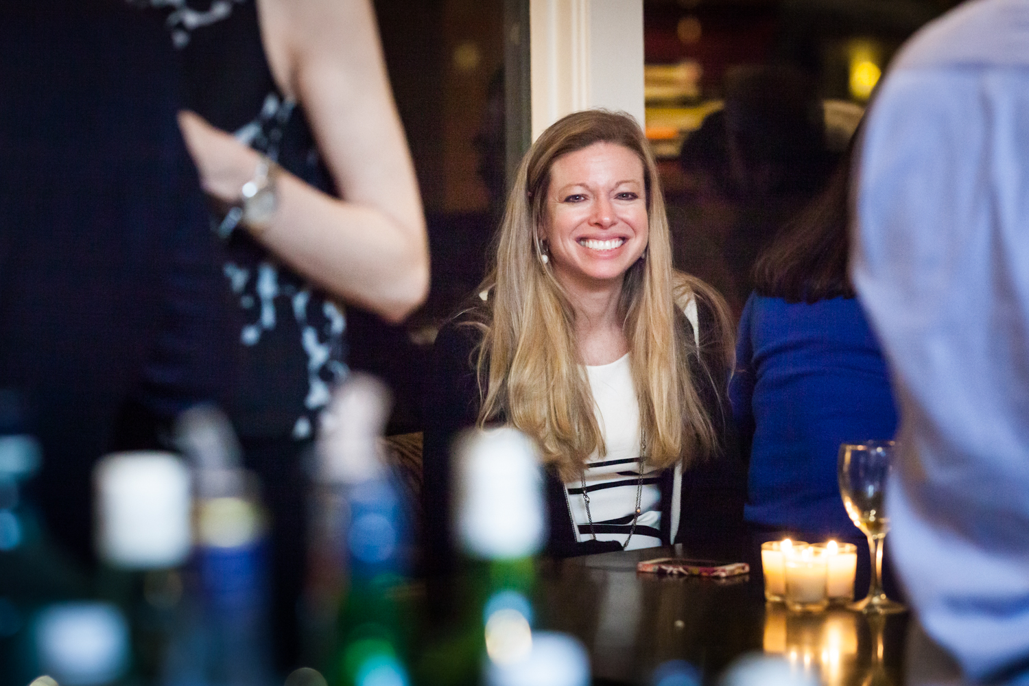 Birthday party photos of woman with blond hair smiling over bar