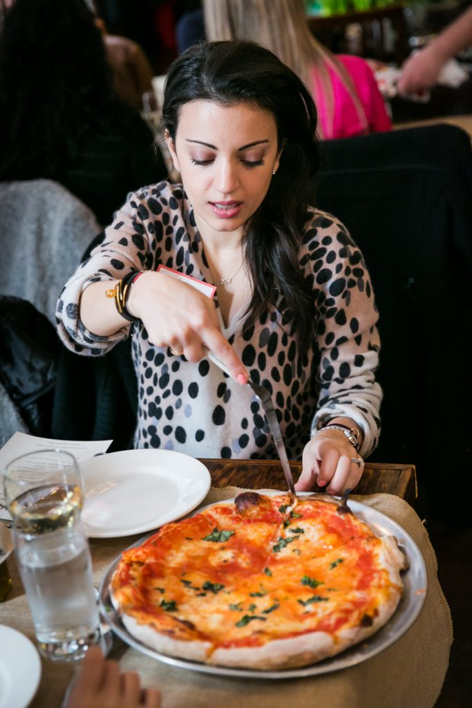 Woman cutting pizza at a NYC bridal shower