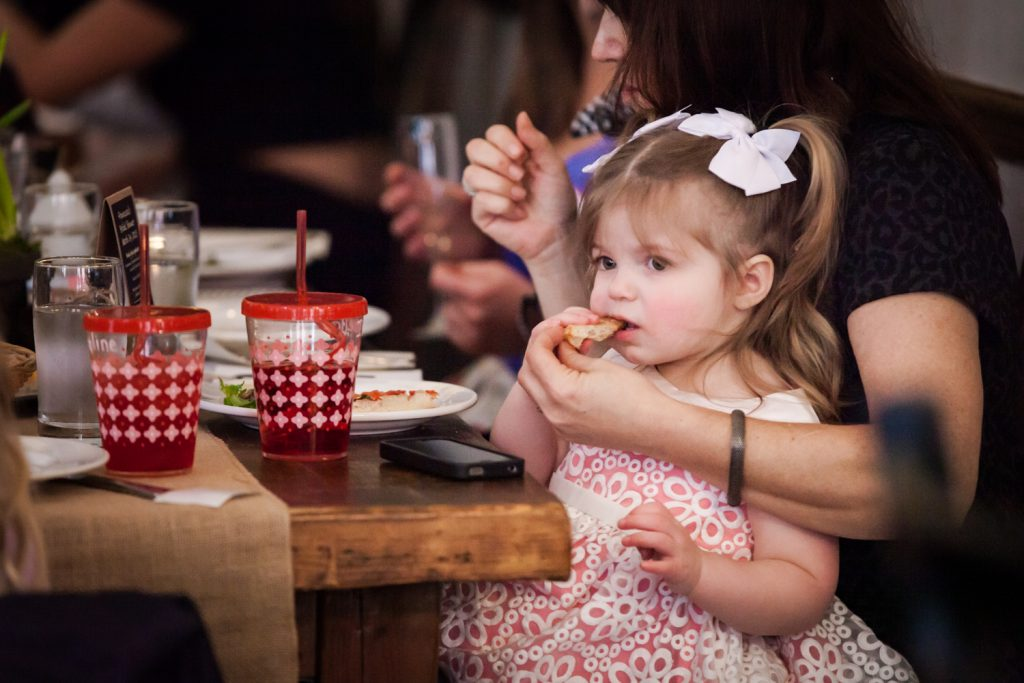 Hand feeding little girl a snack at a NYC bridal shower