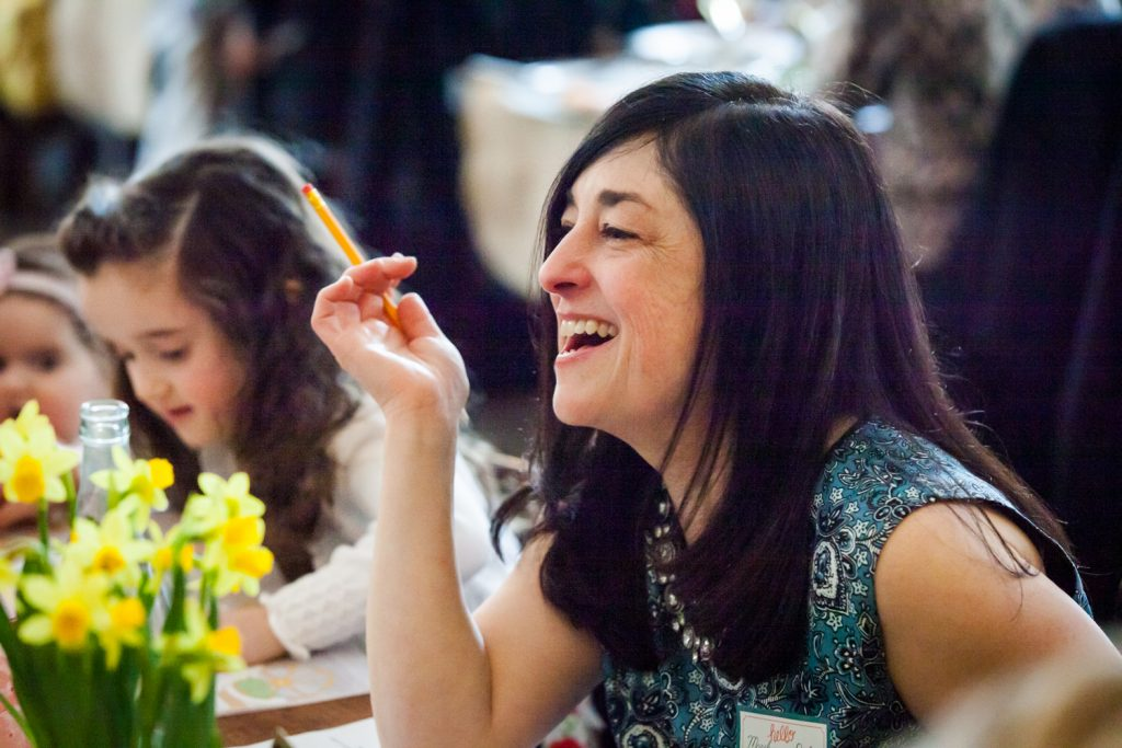 Woman with black hair laughing at a NYC bridal shower