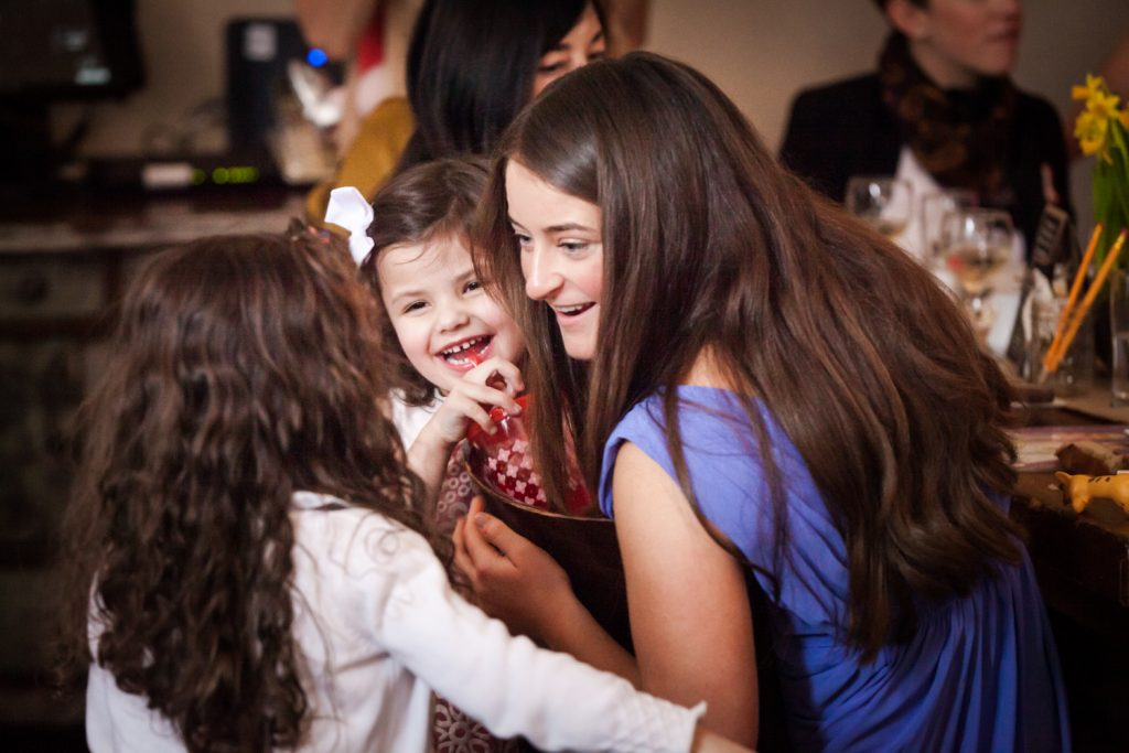 Girl chatting with two little girls at a NYC bridal shower