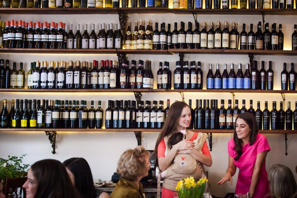 Two women talking with wall of wine bottles in the background