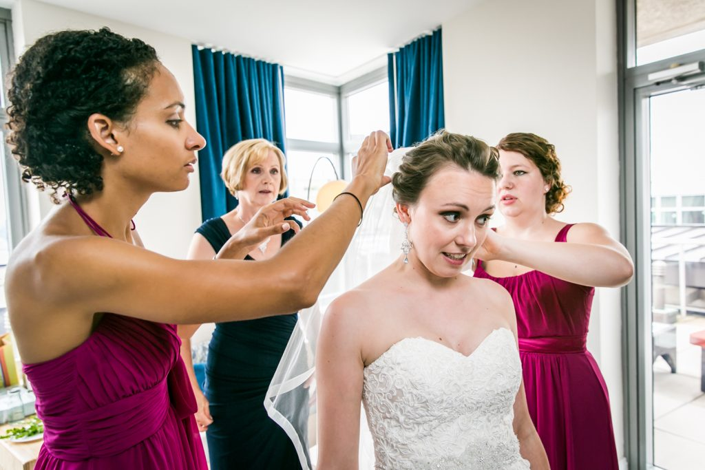 Bridesmaids adjusting veil of bride