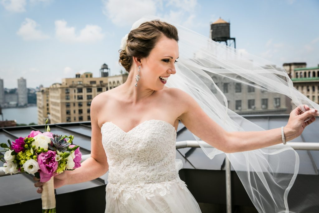 Portrait of bride touching blowing veil on rooftop for an article on how to get the wedding photos you want