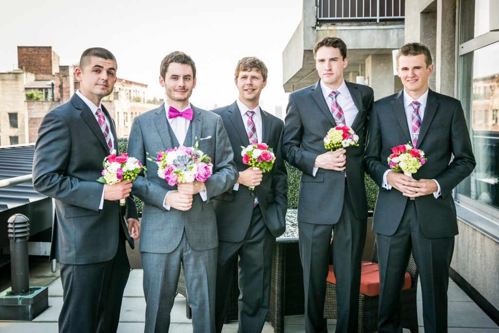 Portrait of groom and groomsmen holding bouquets for an article on how to get the wedding photos you want
