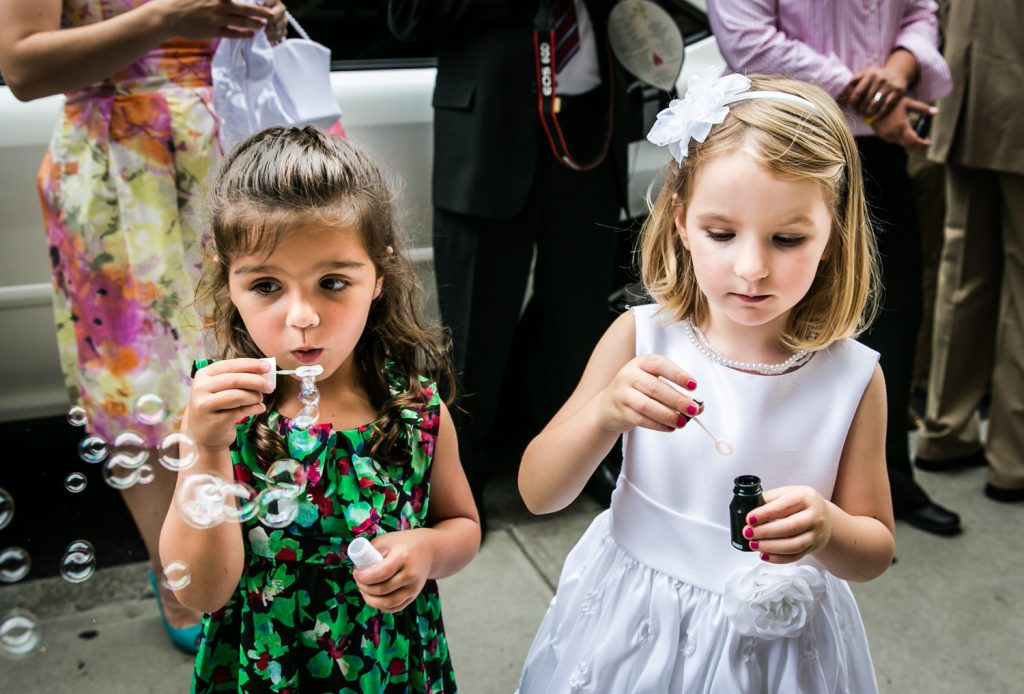 Two little girls blowing bubbles for an article on how to get the wedding photos you want