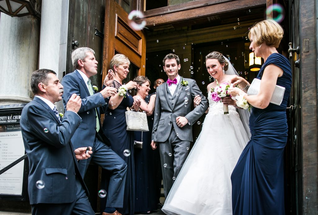 Bride and groom leaving church with guests blowing bubbles