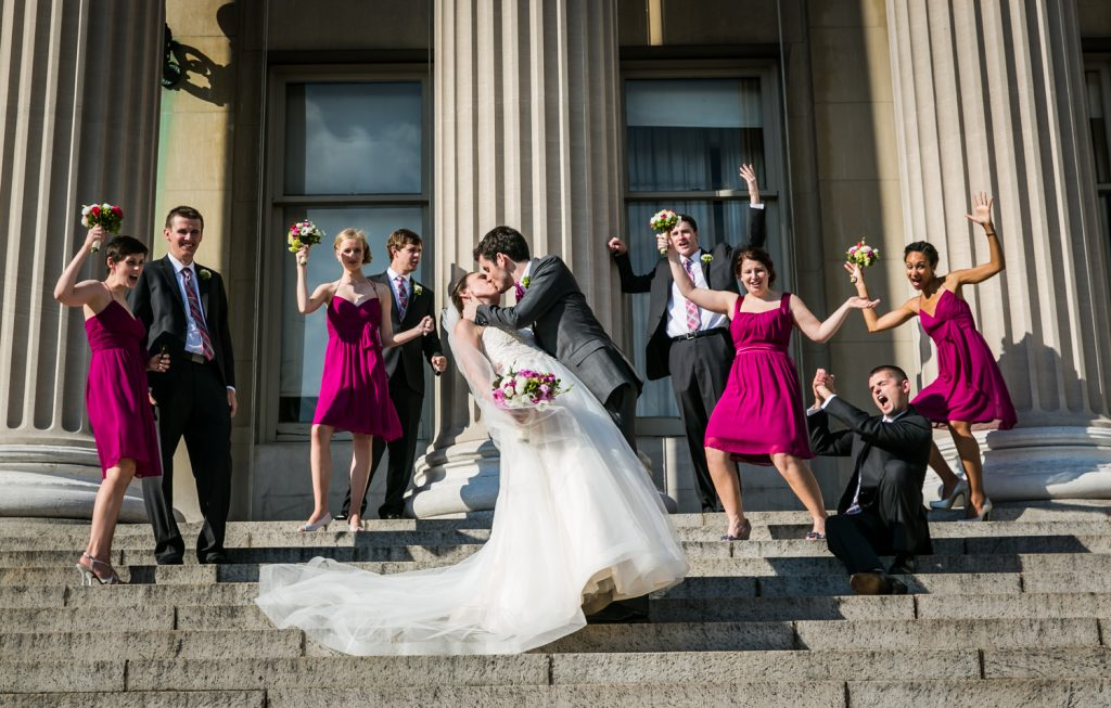 Bride and groom kissing on steps in front of cheering bridal party