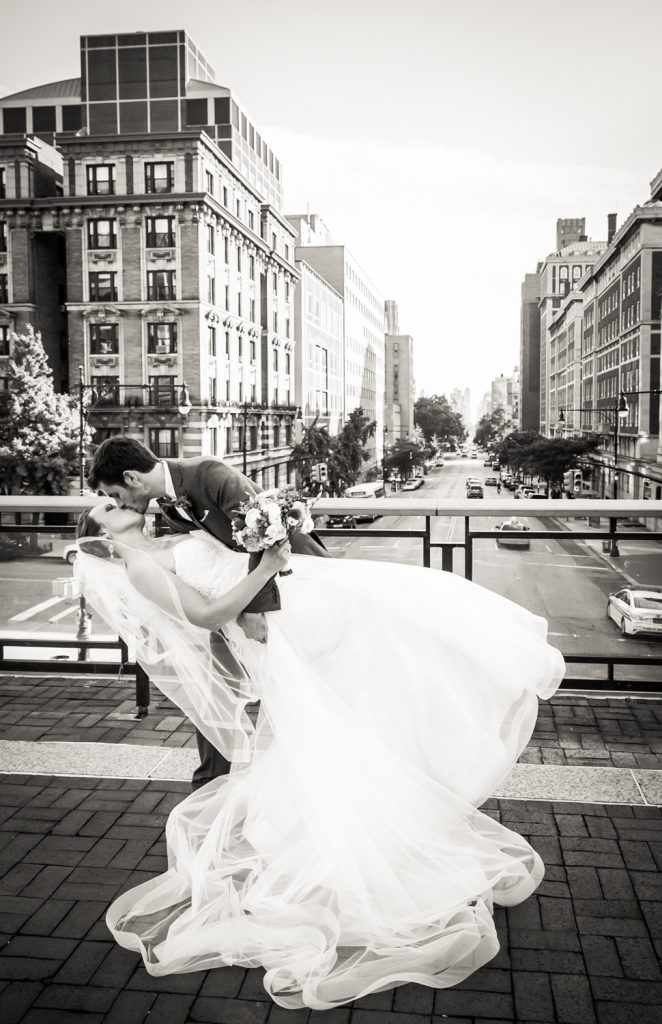 Groom dipping bride on NYC building rooftop