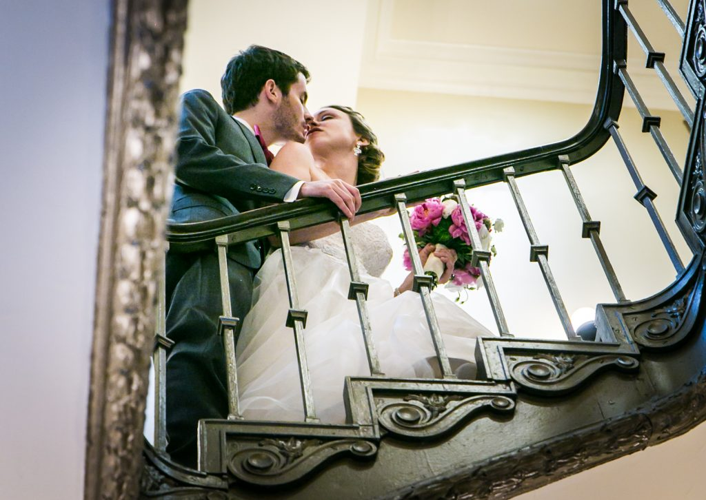 Bride and groom about to kiss on staircase for an article on how to get the wedding photos you want