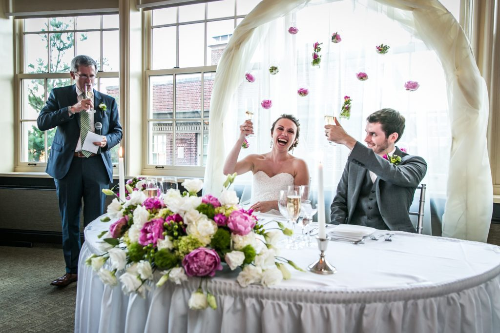 Speech with bride and groom toasting glasses for an article on how to get the wedding photos you want