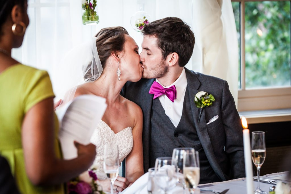Bride and groom kissing at wedding reception for an article on how to get the wedding photos you want