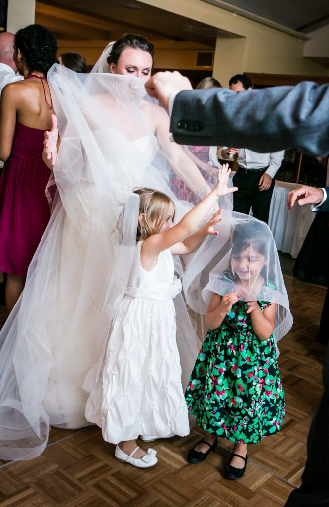 Little girls playing in bride's veil for an article on how to get the wedding photos you want