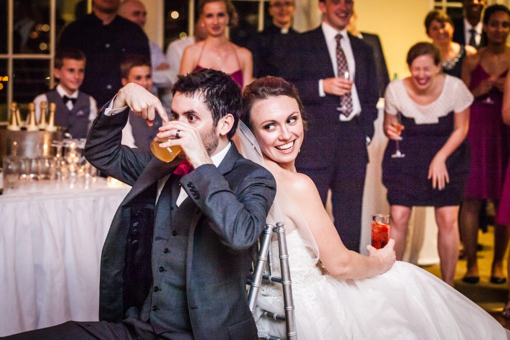 Bride and groom playing drinking game at wedding reception