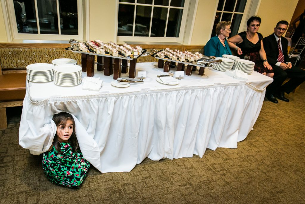 Little girl hiding under table at wedding reception