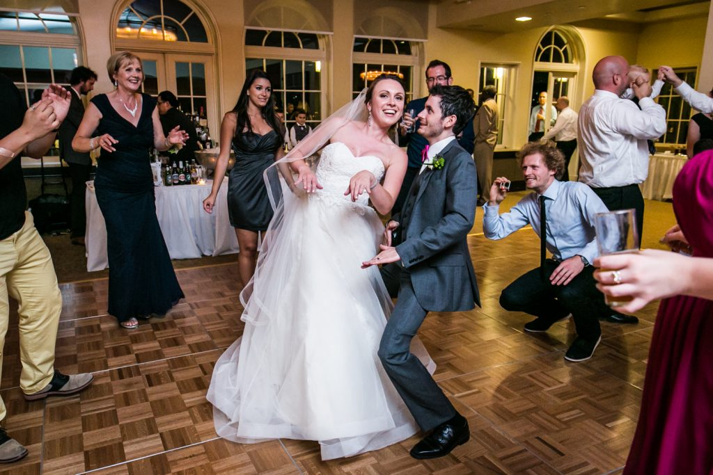 Bride and groom dancing within circle at wedding reception
