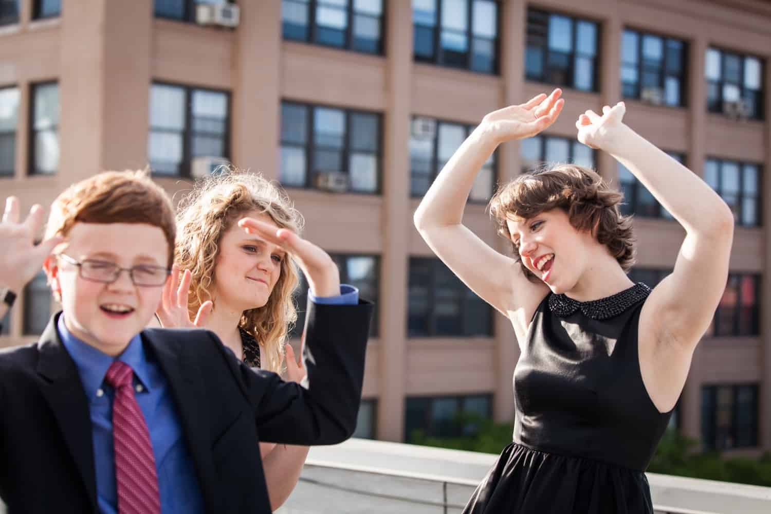 Two girls and one boy dancing with arms raised on roof