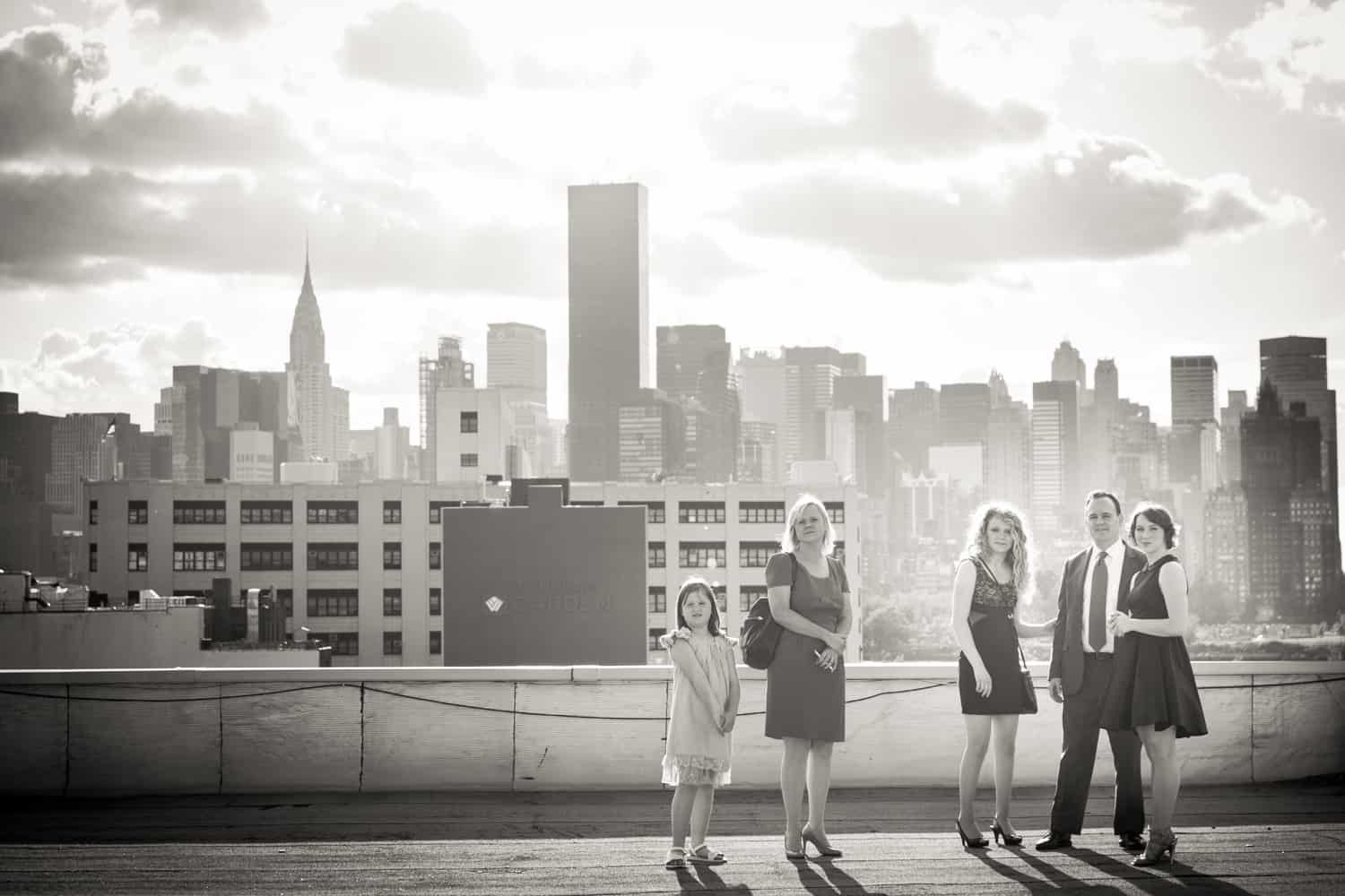Black and white photo of family on roof with view of NYC skyline