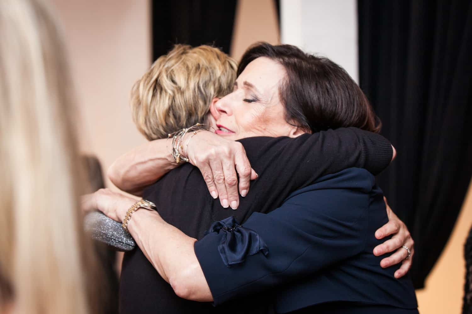 Two women hugging for an article on how to plan the perfect bar mitzvah