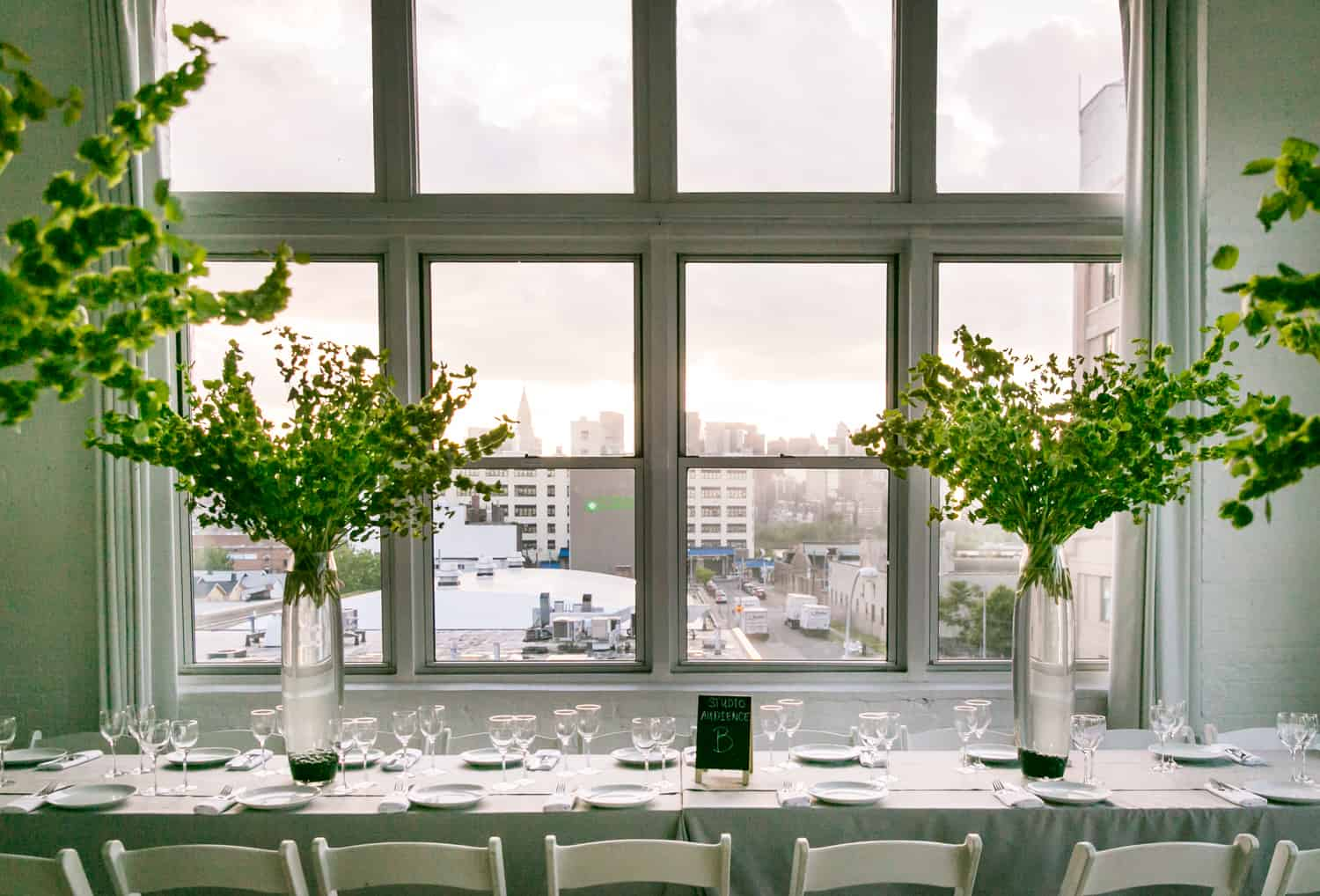 Table setting with tall vases and view of NYC skyline for an article on how to plan the perfect bar mitzvah