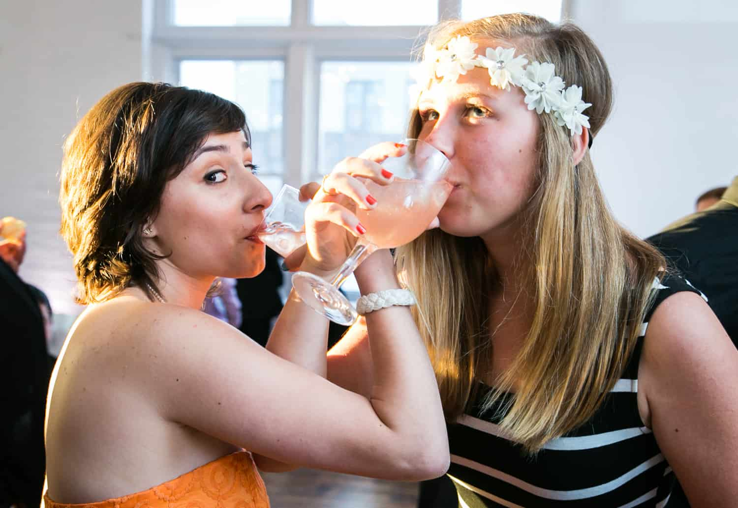 Two girls with entwined arms drinking from glasses for an article on how to plan the perfect bar mitzvah