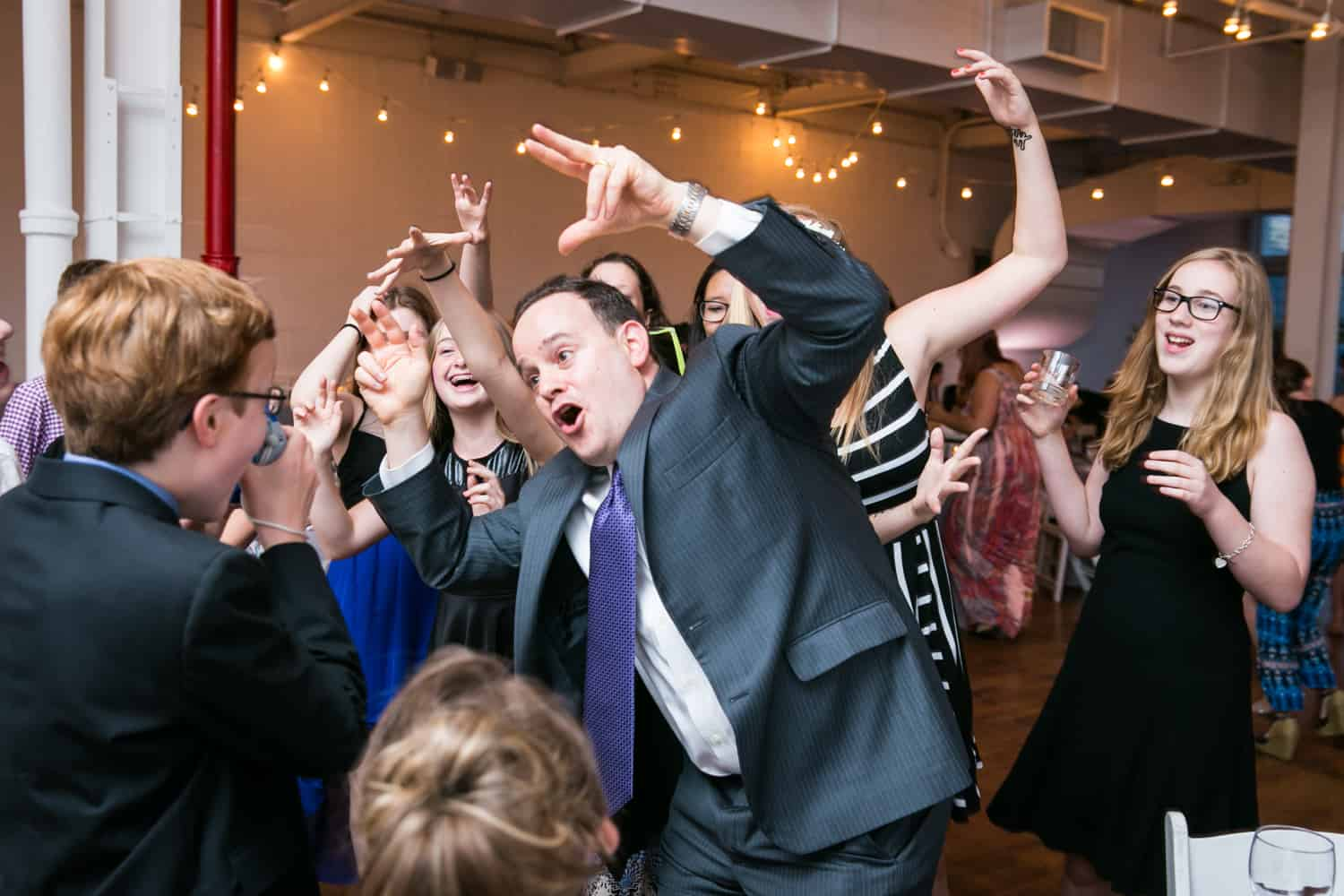 Guests dancing crazy in front of camera for an article on how to plan the perfect bar mitzvah