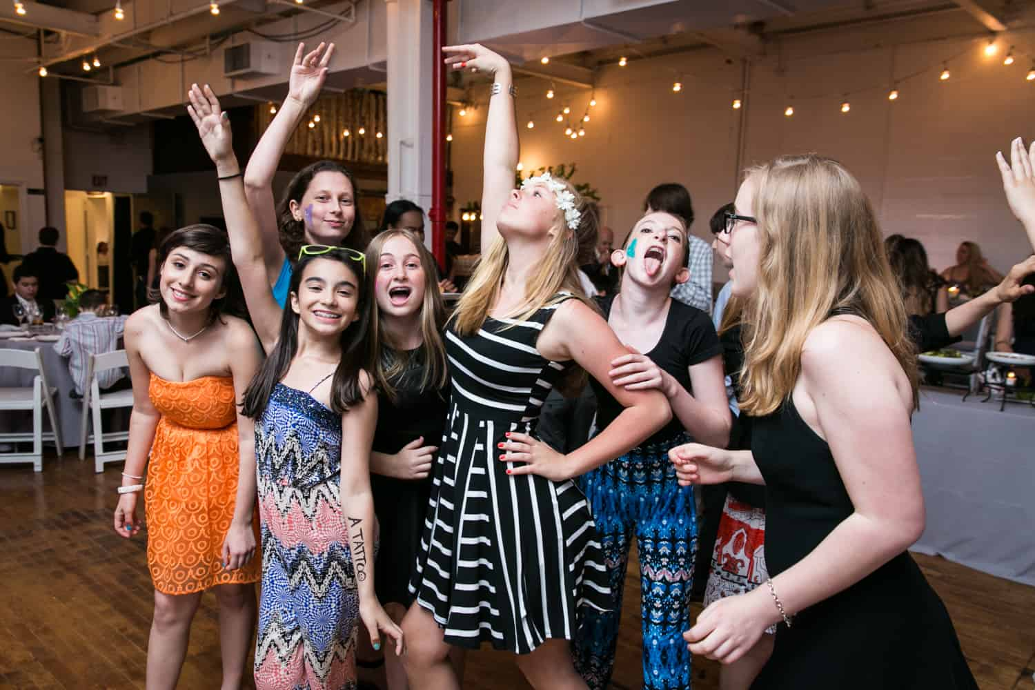 Girls dancing with arms above for an article on how to plan the perfect bar mitzvah