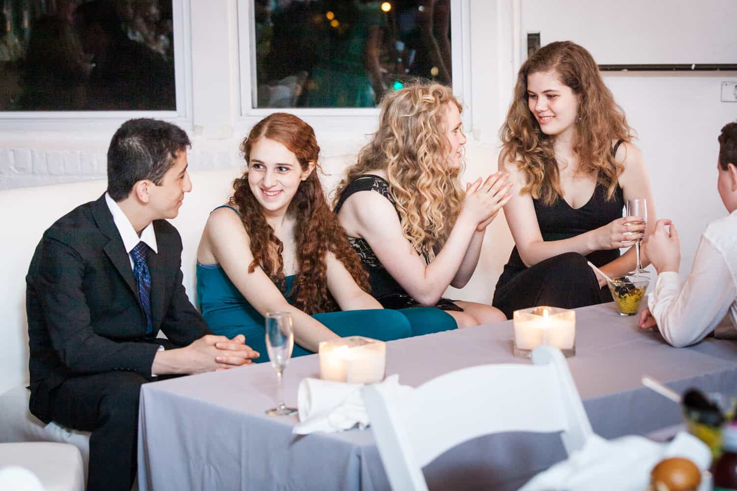 Kids talking at a table for an article on how to plan the perfect bar mitzvah