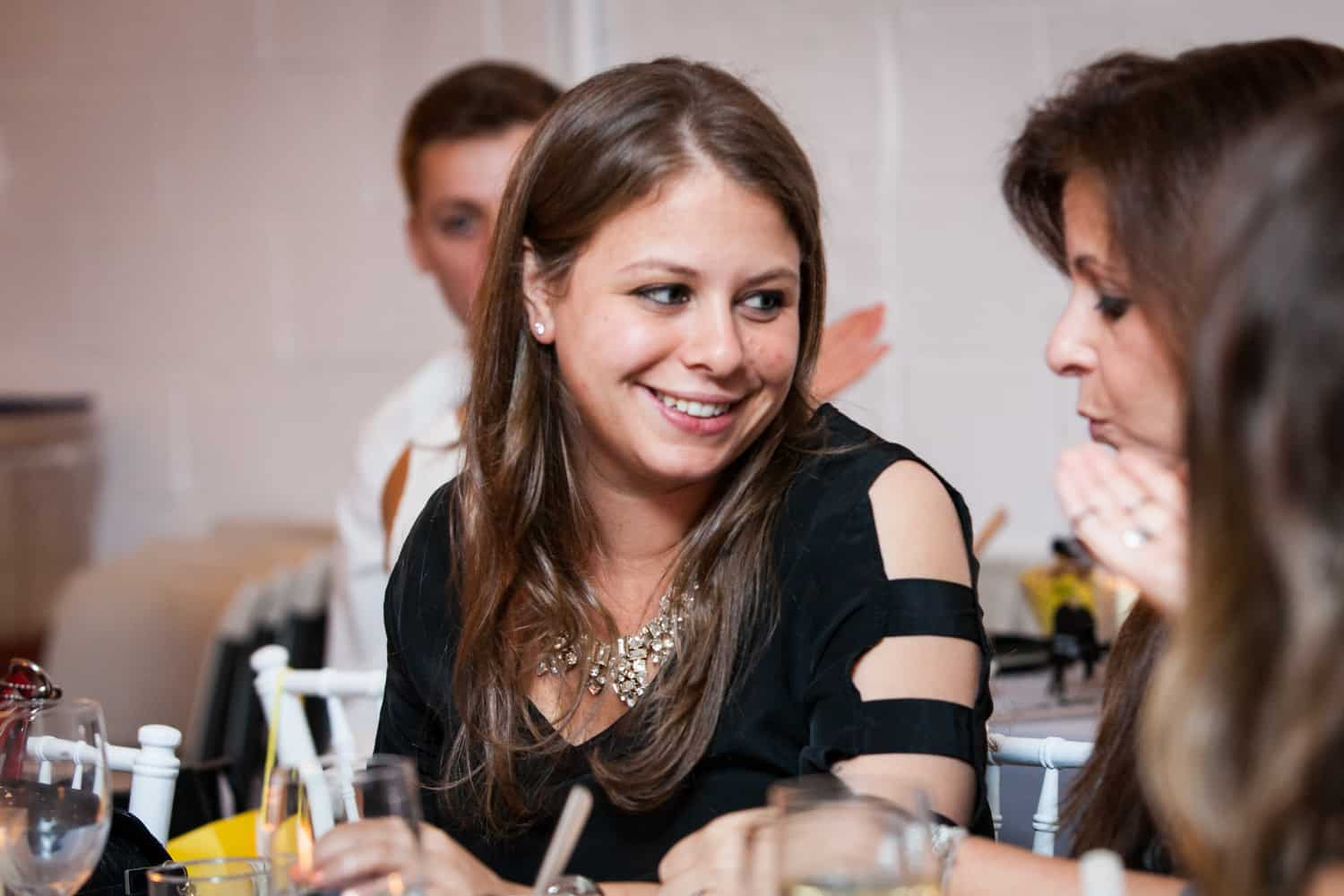 Girl talking to another guest at table for an article on how to plan the perfect bar mitzvah