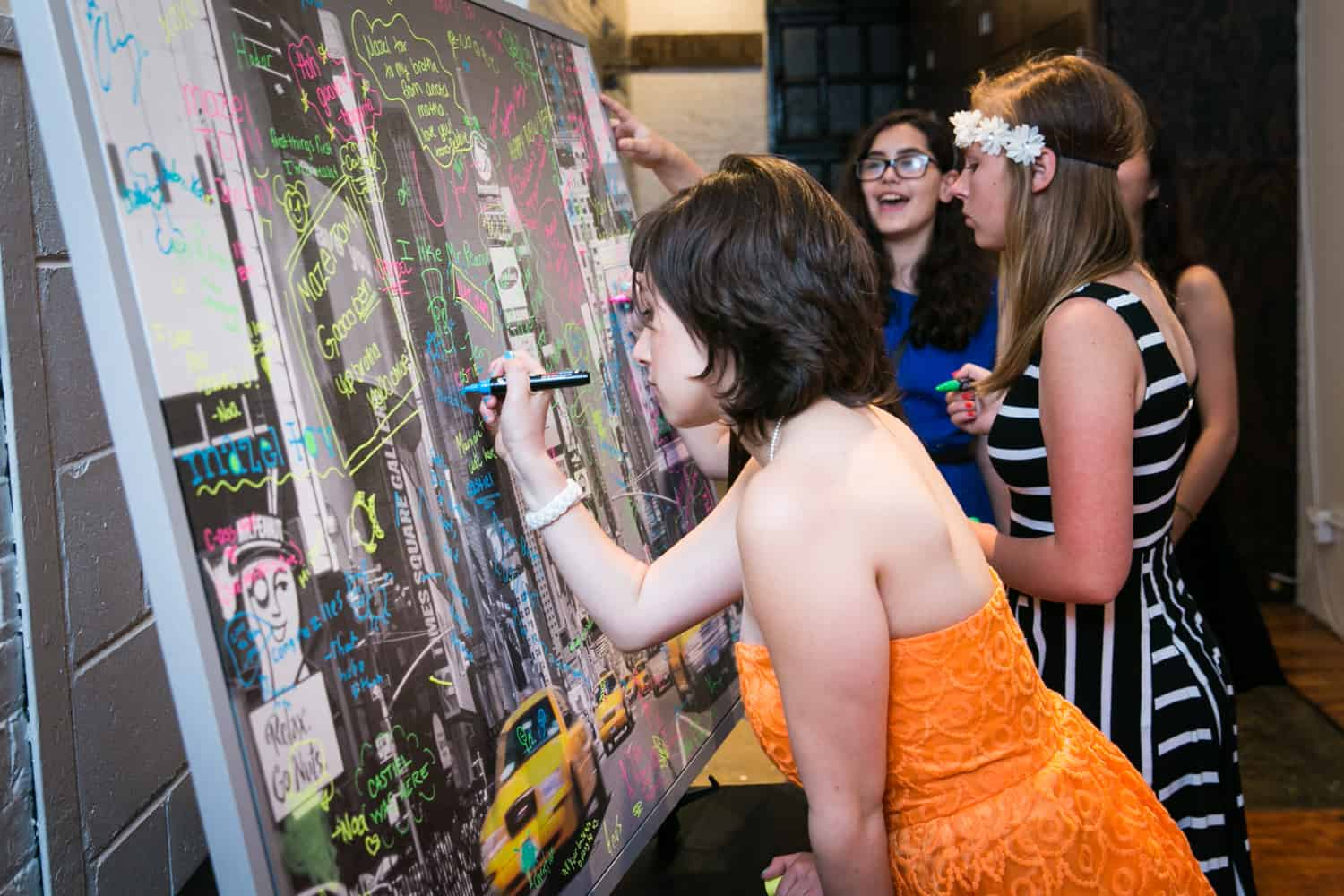 Girl signing framed guest book for an article on how to plan the perfect bar mitzvah