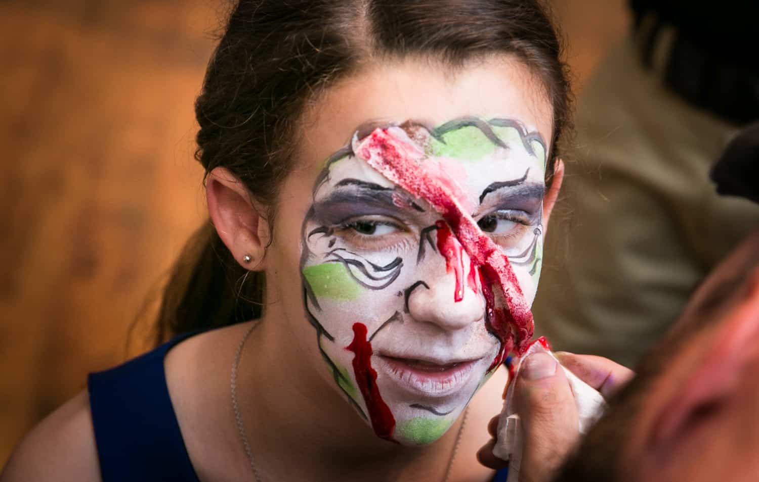 Close up of girl getting zombie makeup painted for an article on how to plan the perfect bar mitzvah