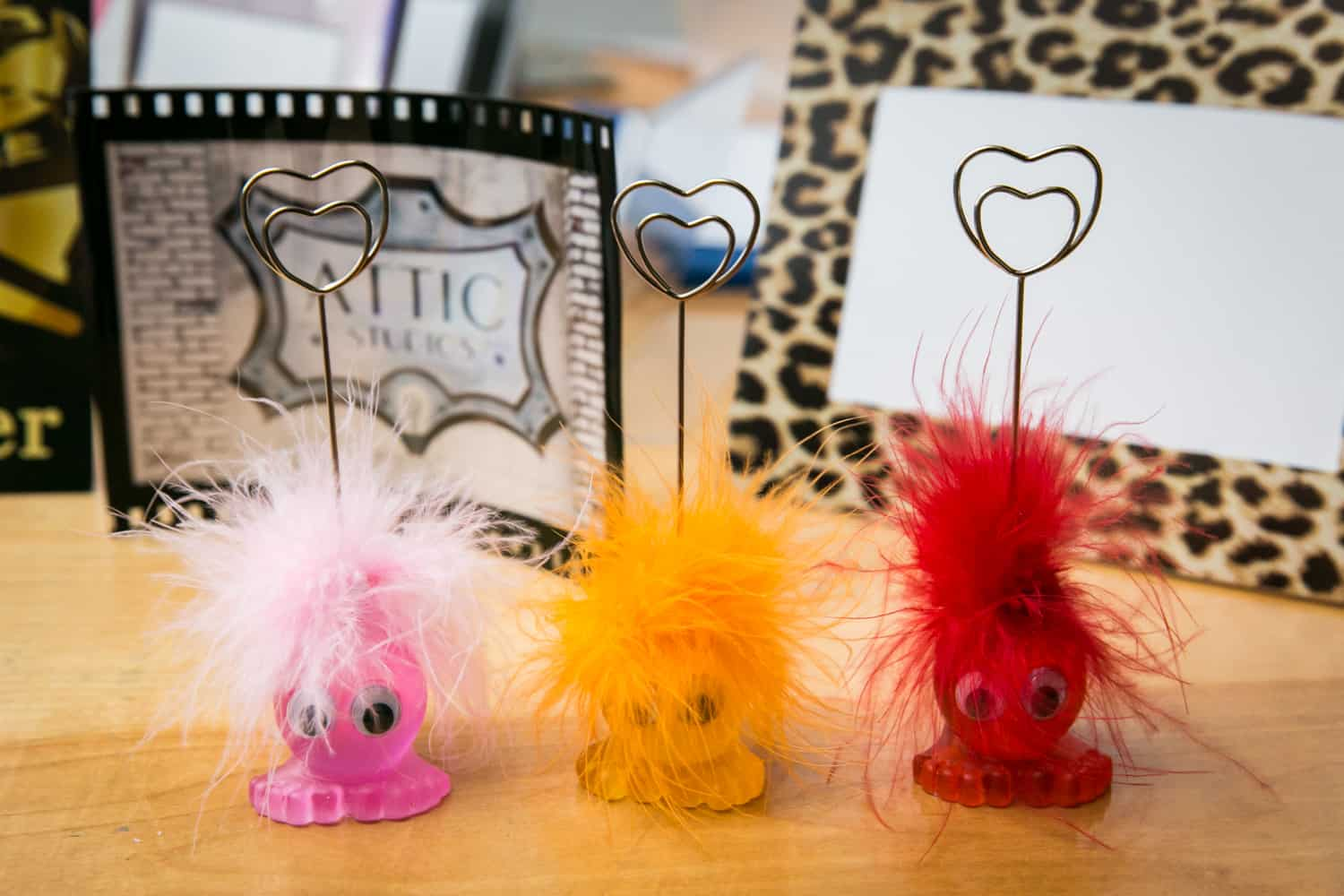 Three colorful, fuzzy photo holders on table