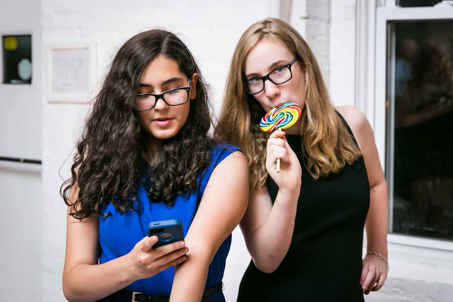 Girl with cell phone and girl licking lollipop for an article on how to plan the perfect bar mitzvah