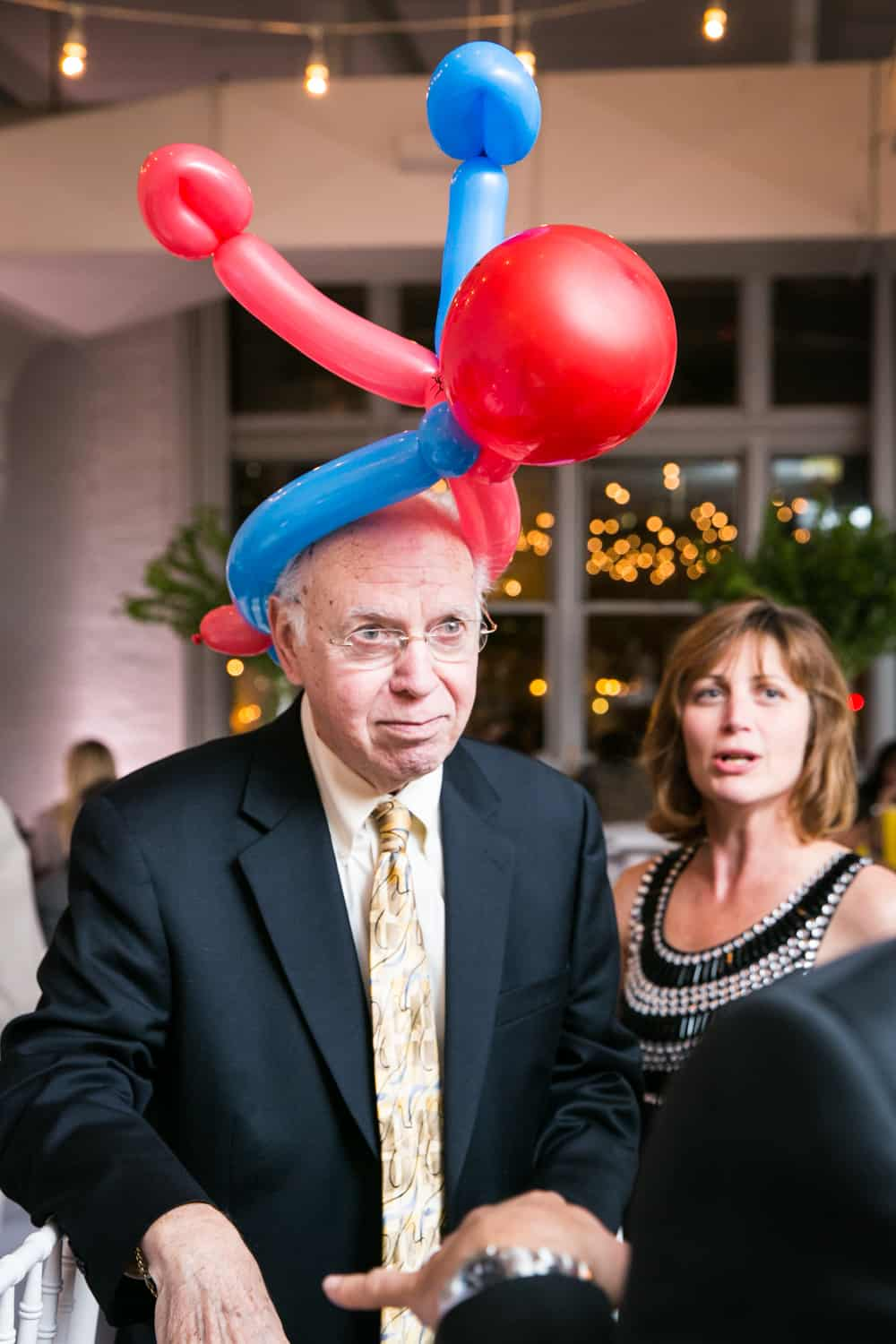 Man wearing red and blue balloon for an article on how to plan the perfect bar mitzvah