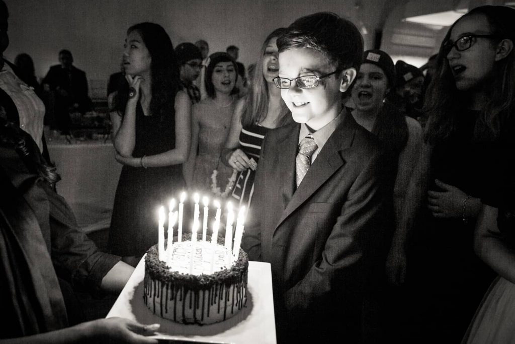 Black and white photo of boy blowing out birthday candles