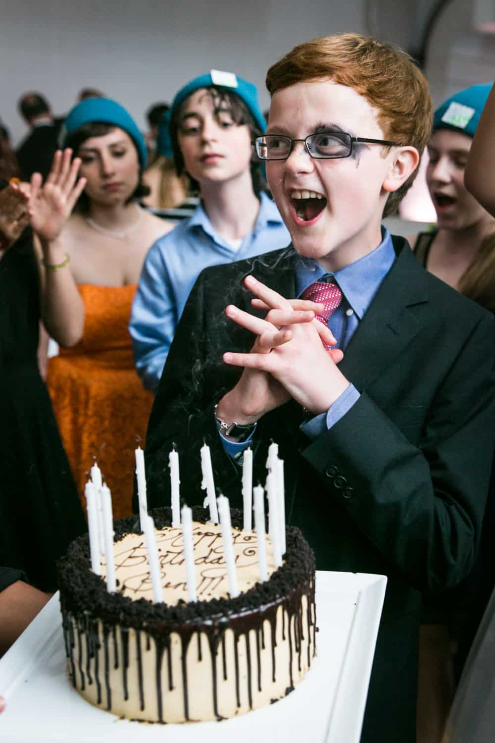 Boy celebrating after blowing out candles for an article on how to plan the perfect bar mitzvah