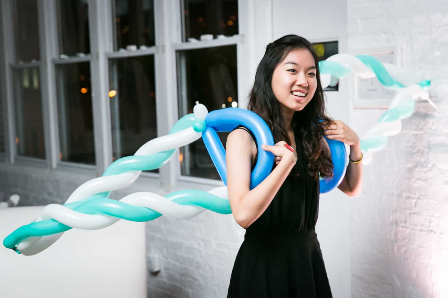 Girl with blue and white balloon wings for an article on how to plan the perfect bar mitzvah