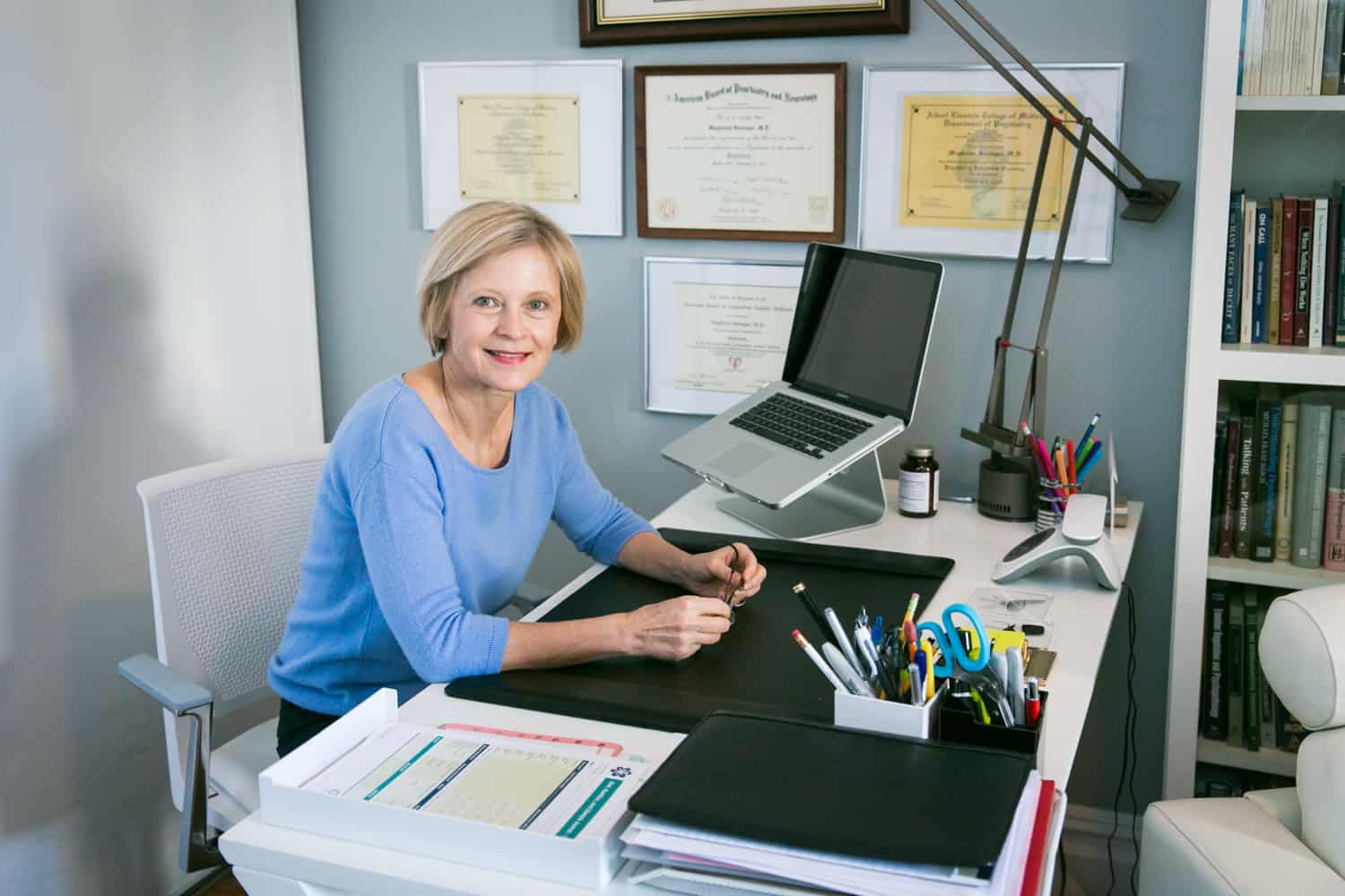 Professional portraits of a psychiatrist smiling at her desk