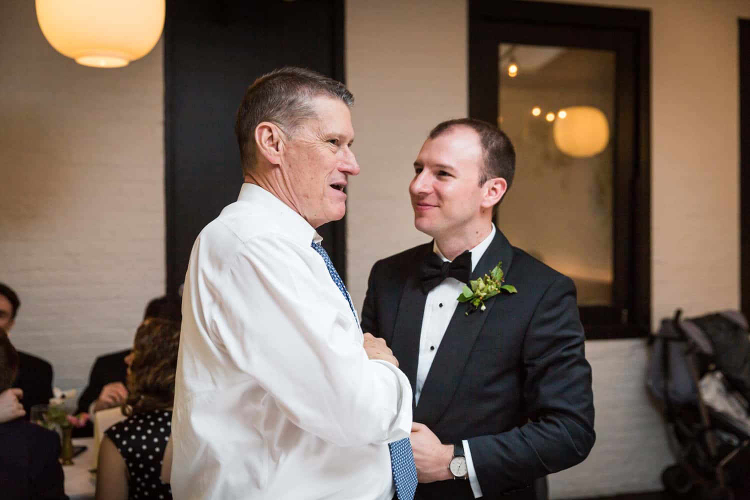 Groom speaking with guest at wedding reception