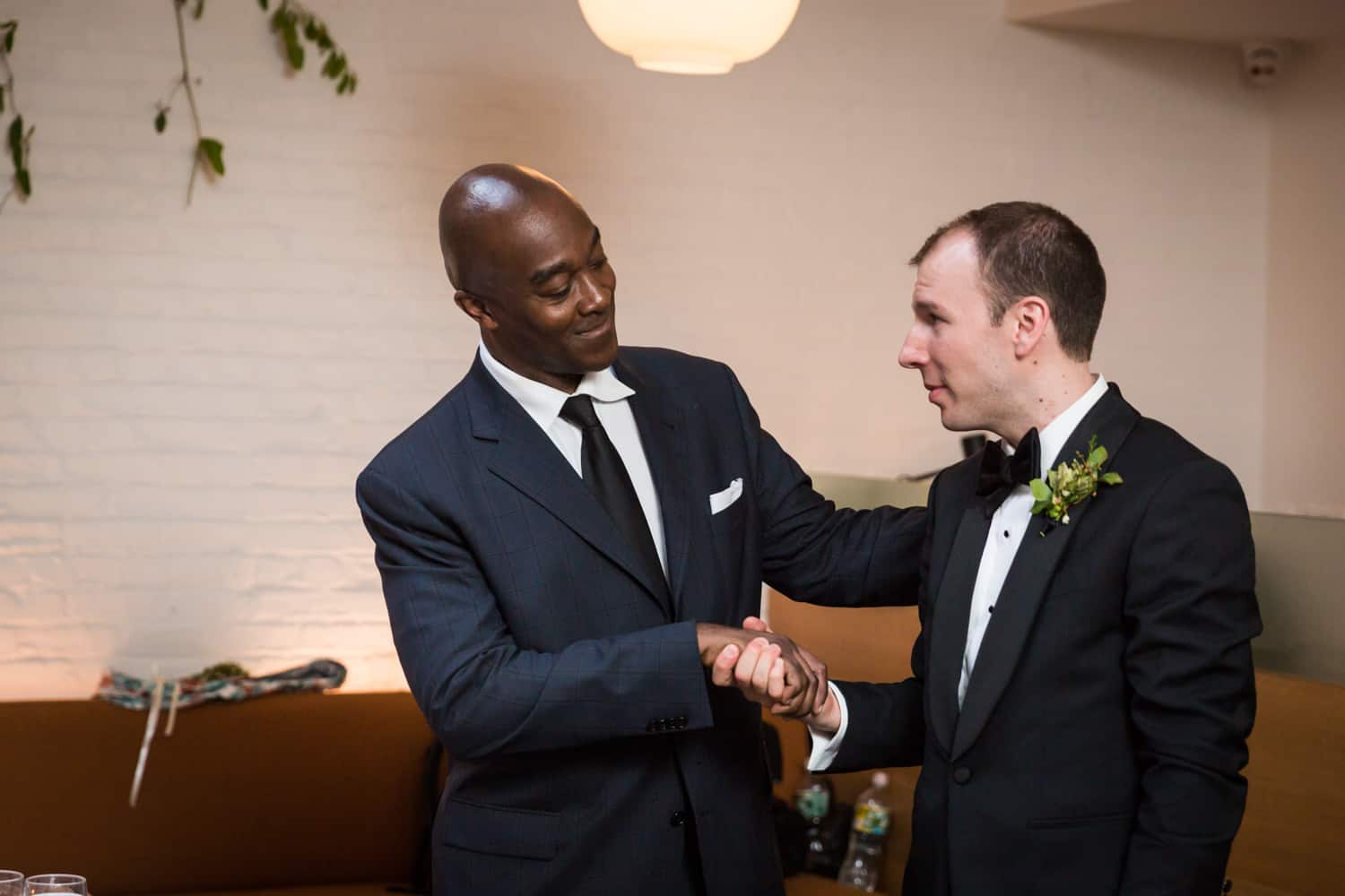 African American guest shaking hands with groom
