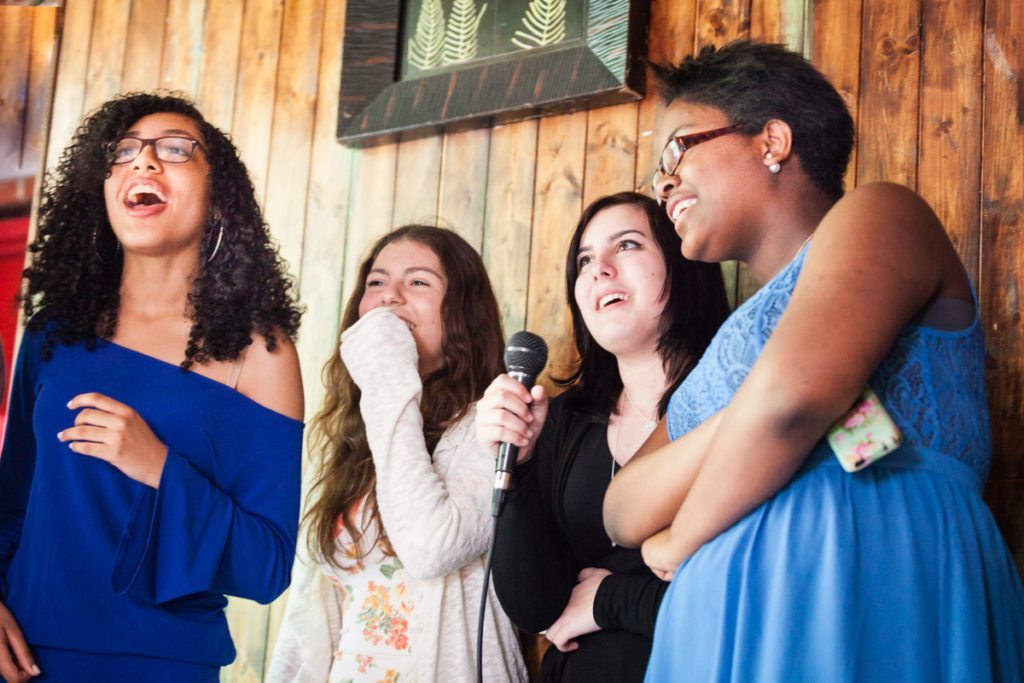Kids performing karaoke, by NYC bat mitzvah photographer, Kelly Williams