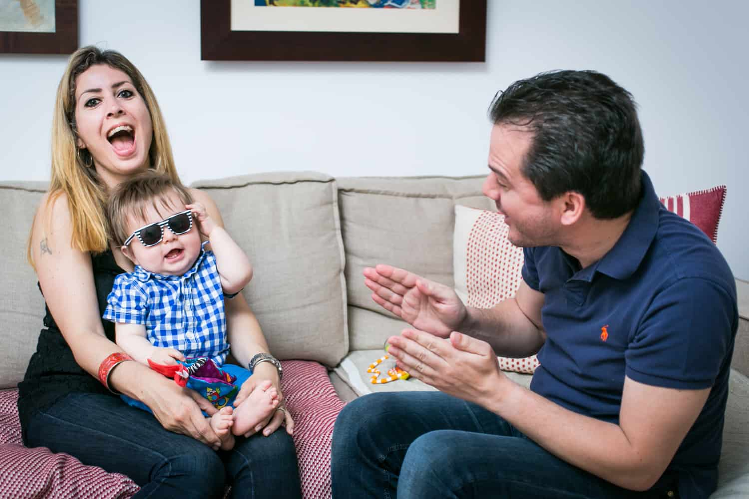 Father entertaining mother and baby wearing sunglasses