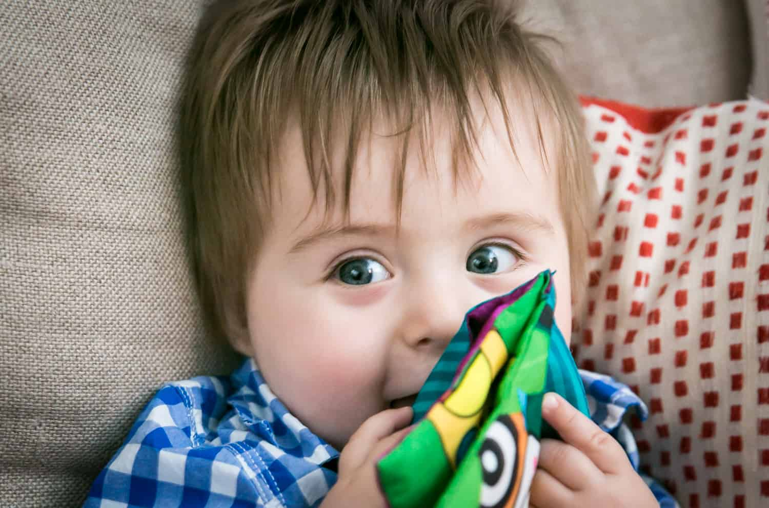 Baby boy playing with cloth book