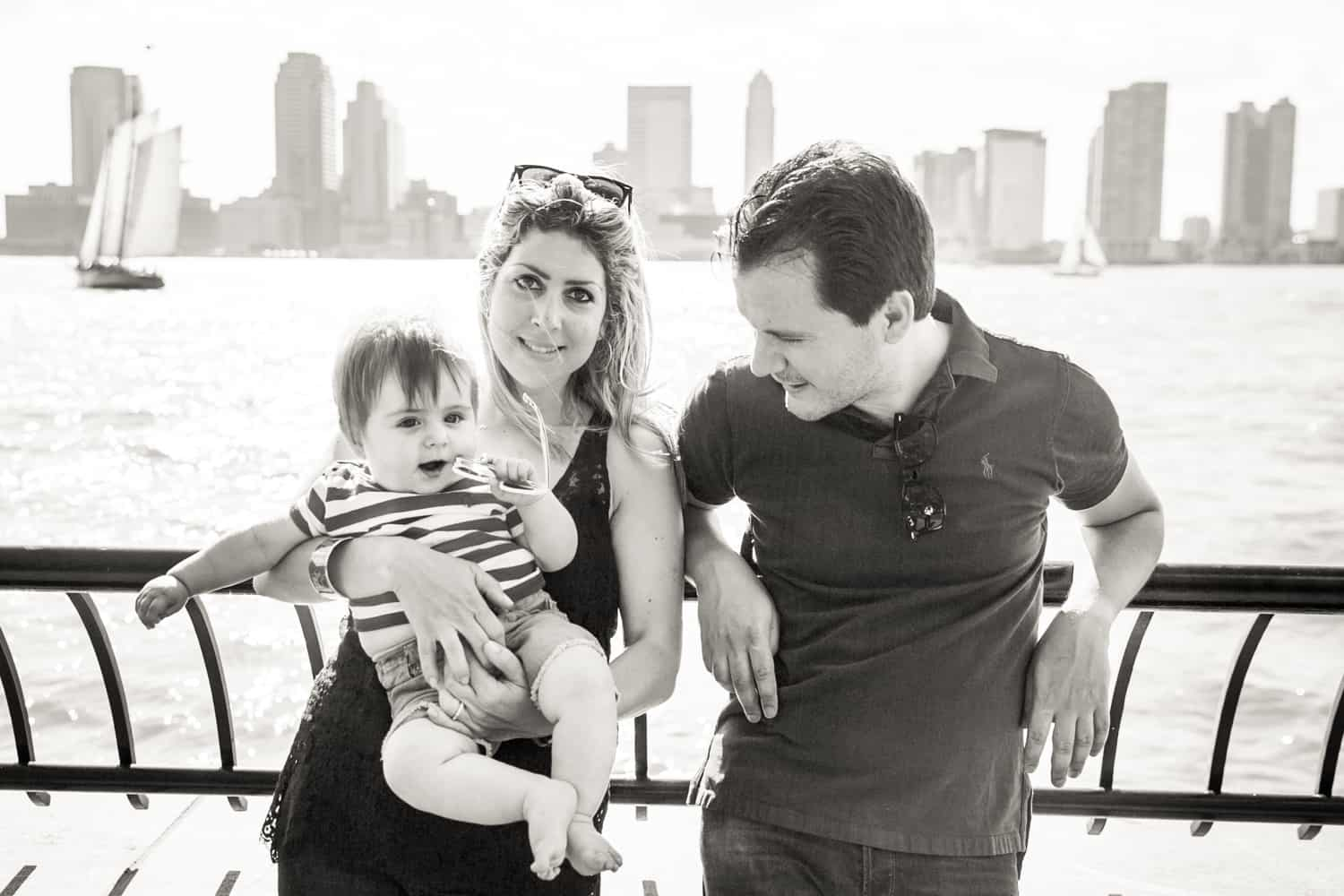 Black and white photo of parents with baby in front of NYC waterfront