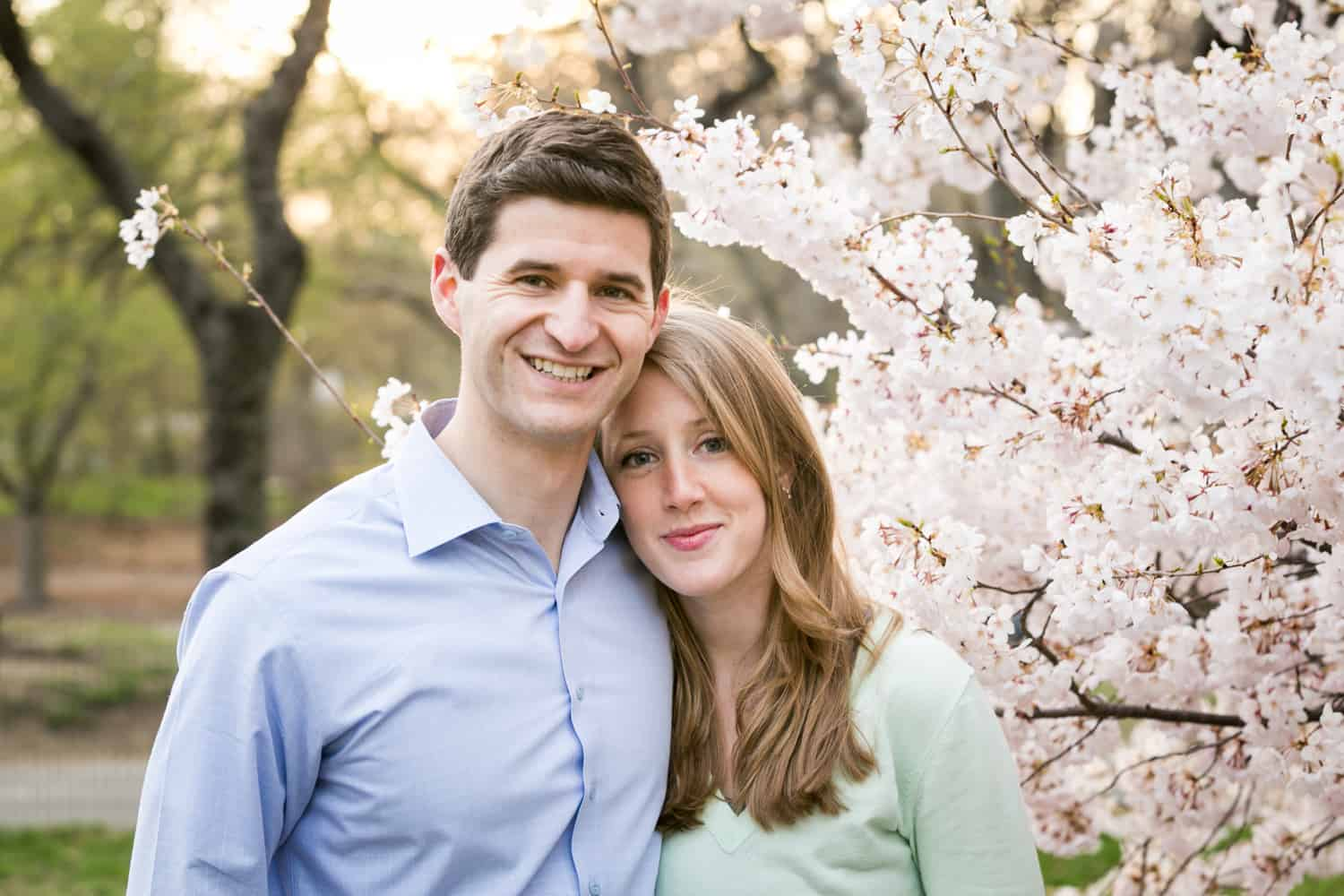Couple standing in front of cherry blossoms in Central Park for an article ranking the best places to see cherry blossoms in NYC