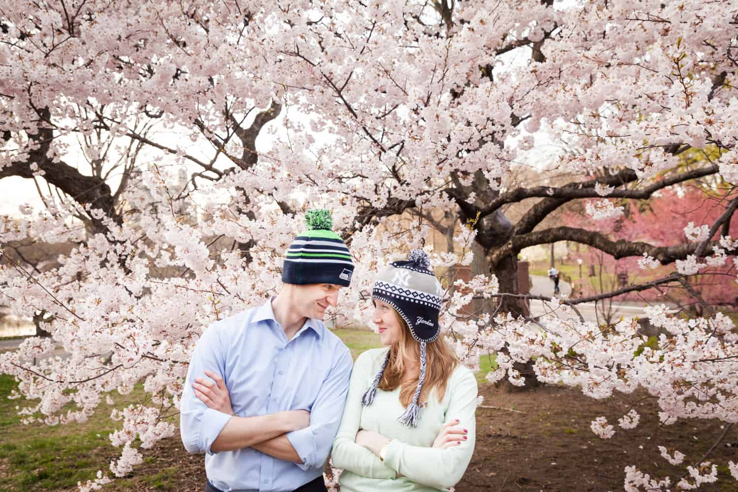 Couple with folded arms and wearing funny knit hats in front of cherry blossom trees in Central Park