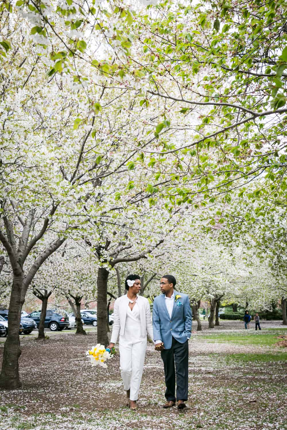 Couple walking under cherry blossom trees in Flushing Meadows Corona Park for an article ranking the best places to see cherry blossoms in NYC