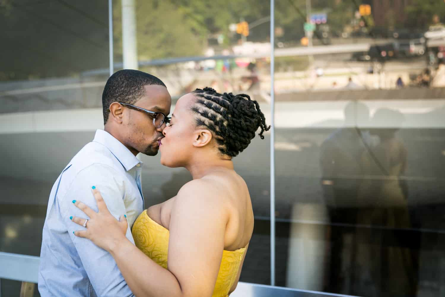 Couple kissing in front of glass wall with reflection