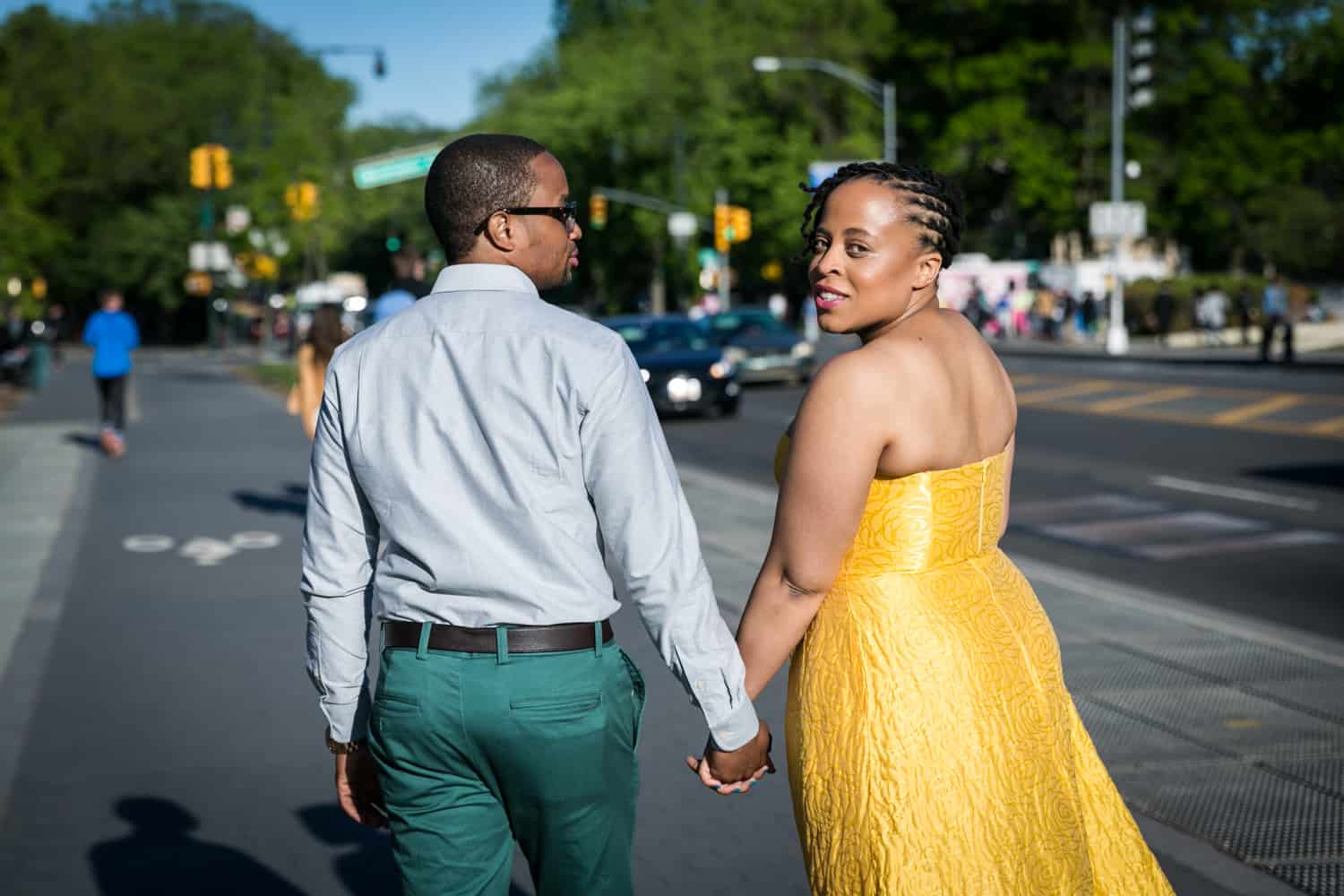 Couple holding hands and walking down sidewalk and woman looking over shoulder